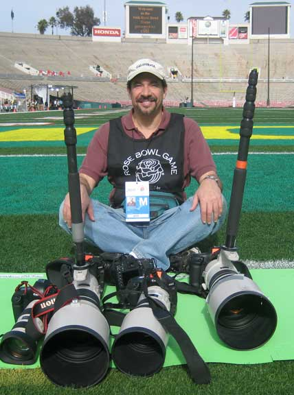 Dr. P sitting and smiling at the camera in the end zone with his camera equipment 4 hours before the Rose Bowl game