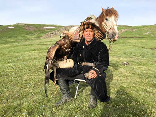 A proud Kazakh nomad with his horse and golden eagle posing for us