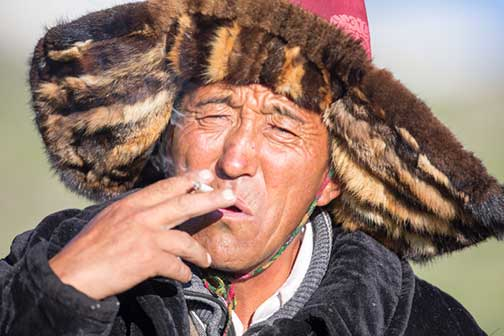 Kazakh nomad of western Mongolia smoking a hand rolled cigarette