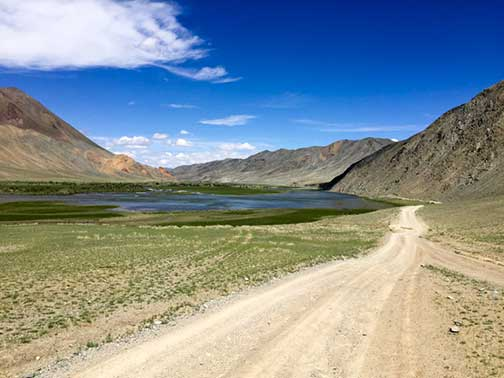 Summertime on a dusty dirt road in the mountains of western Mongolia along a river