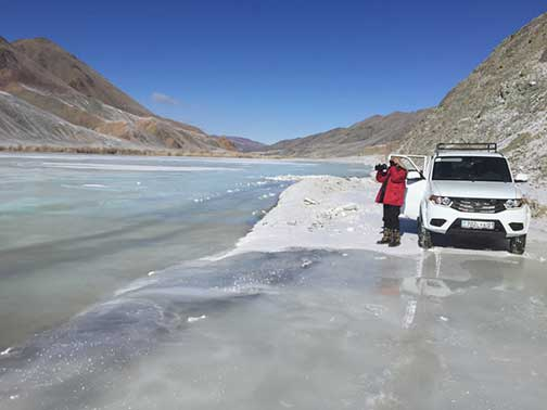 Wintertime on a frozen road in the mountains of western Mongolia along a river