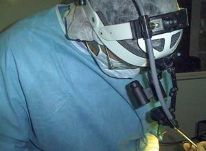 Surgeon with magnifying loop on head